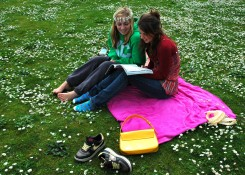photo credit: On a pink, green, and white cloud, two young women reading a book at Greenlake, with a daisy chain in a field of flowers, Seattle, Washington, USA via photopin (license)