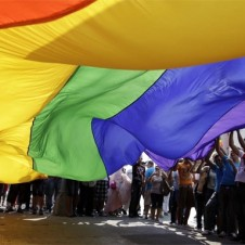 Gay pride celebrants with large rainbow flag