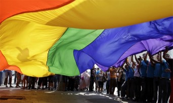 Gay pride celebrants with large rainbow flag