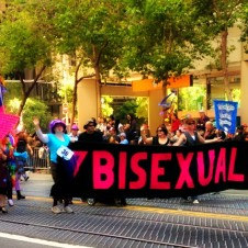 Parade participants carrying a large bisexuals banner