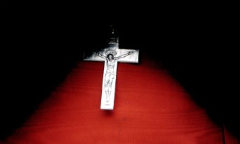 Small cross on wooden background