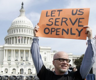 "Protester holds ""Let us serve openly"" sign near US Capitol building"