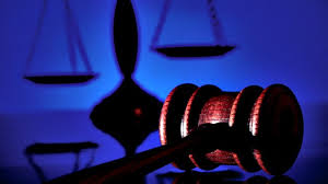 Gavel and legal scales with blue background