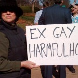 "Woman holding sign that says ""Ex-gay = harmful hoax"""