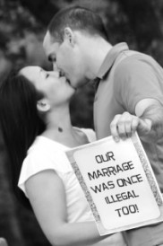 "Biracial couple kissing with sign ""our marriage was once illegal too."" Photo by Jodi Rives Meier for Kiss4Equality.org"