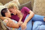 Lesbian couple embracing on couch