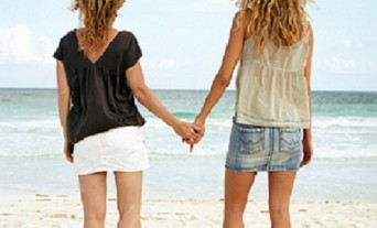 Two women holding hands at beach, rear view