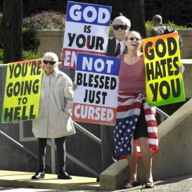 Westboro Baptist Church members with signs