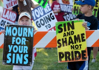 Children holding Westboro Baptist Church signs