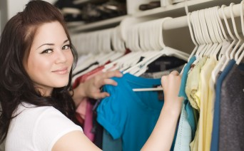 Woman looking through clothes in closet