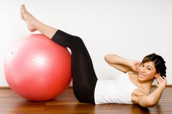 Woman using an exercise ball to do sit-ups