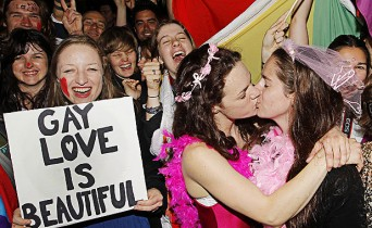 CHRIS SKELTON/Fairfax NZ LOVING SUPPORT: Rosie Jimson-Healey holds a sign as Emma Fawcett and Phillipa Walker kiss during a rally outside Parliament as the Marriage (Definition of Marriage) Amendment Bill is debated inside.