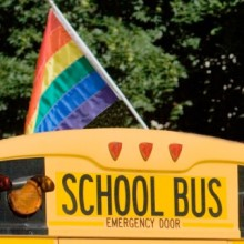 Gay pride flag on top of a school bus