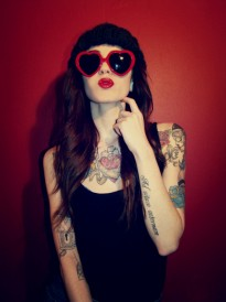 Woman with heart sunglasses, tattoos, long hair