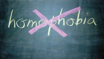 Homophobia written on chalkboard and crossed out
