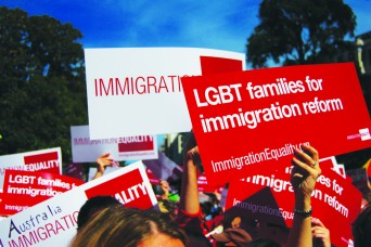 Protestors holding signs for LGBT immigration reform
