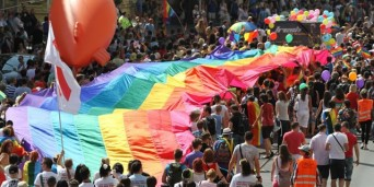 Celebrants in Prague Pride parada carry rainbow flag