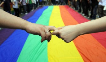 Lesbians holding hands in front of large Pride flag