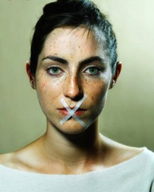 Woman with tape on her mouth as statement.