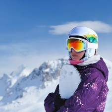 woman snowboarding with rainbow goggles