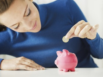 woman-putting-money-into-a-piggy-bank